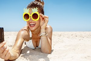 Smiling woman in pineapple glasses taking selfie at sandy beach