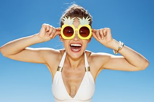 Smiling woman in swimsuit and funky pineapple glasses at beach