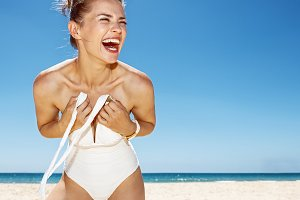 Smiling woman tying white swimsuit at sandy beach on sunny day