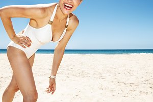 Closeup on happy woman in white swimsuit at sandy beach