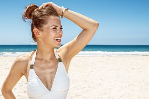 Happy woman in white swimsuit at sandy beach looking aside