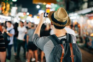 Young Asian traveler taking photo with mobile phone in Khaosan road in Bangkok, Thailand