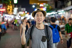 Asian tourist pointing at the back in Asia night market