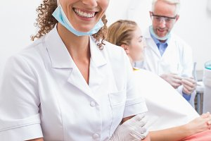Dental assistant smiling at camera with dentist and patient behind
