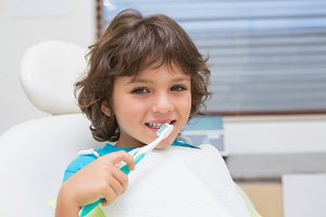 Little boy in dentists chair using toothrbrush