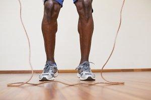 Muscular man skipping in gym