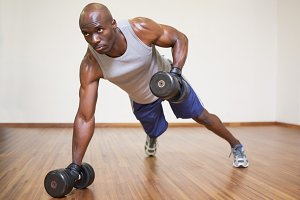 Muscular man doing push ups with dumbbells in gym