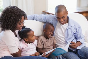 Happy family sitting on couch together reading book