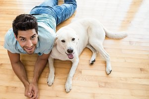 Attractive man lying on floor with his labrador