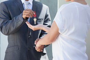 Estate agent giving house key to buyer