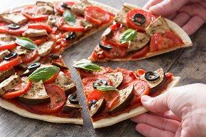 Hands taking vegetarian pizza
