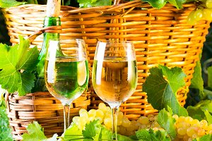 Two glasses and bottle of white wine basketof grapes