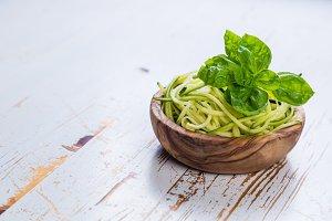 Raw zucchini pasta on white background