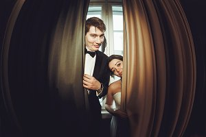 Funny newlyweds behind curtains