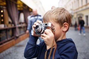 Cute photographer boy holding old film camera
