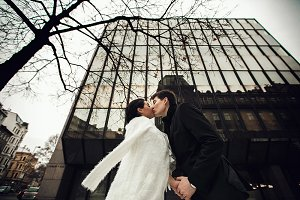 Newlyweds kiss under a huge building