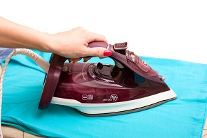 Steam iron in a female hand isolated on white background