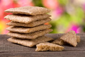stack of crisp bread on a wooden table with blurred garden background
