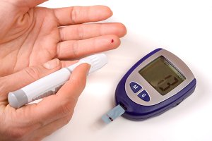 The blood glucose meter with a hand isolated on white background