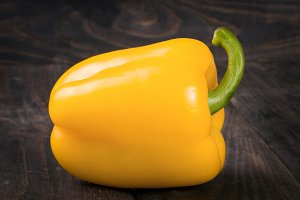 yellow sweet pepper on black wooden background
