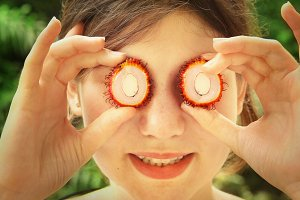 teen girl with cut rambutan fruit half eyes