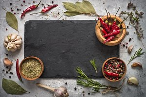 Black slate board, herbs and spices.