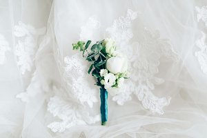 Beautiful boutonniere on white wedding dress, closeup