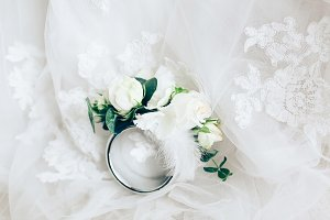 Beautiful boutonniere with ring on white wedding dress, closeup