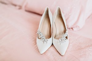 Bride's shoes for wedding day on bed sheet. Selective focus