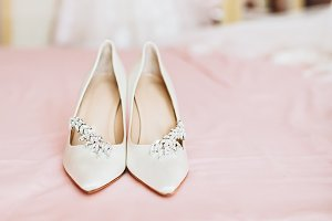 Bride's shoes for the wedding day on bed sheet