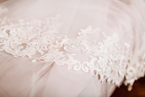 White Wedding dress on bed sheet close-up