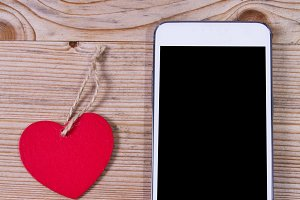 Heart-shaped tag and mobile phone on wooden background