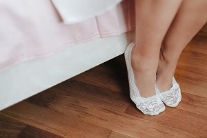 Beautiful legs. Bride's cute ankle is resting on bed.