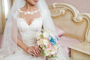 Bride in dress on bed holding wedding bouquet