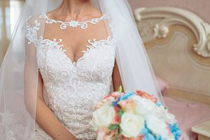 Bride in wedding dress on bed, beautyful bouquet