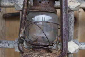 Old kerosene lamp hanging on a metal grid