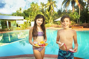 teen kids with fruit on swimming pool background