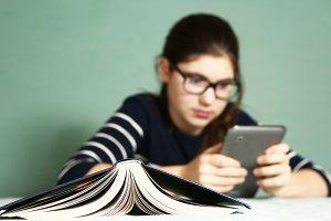 teenager girl in myopia glasses play online game