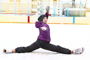 teenager girl on the skating rink make split