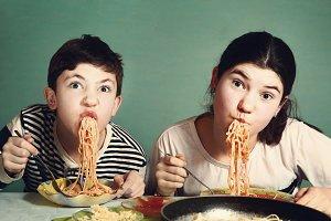 happy teen siblings boy and girl eat spaghetti