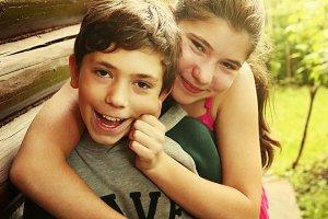 siblings boy girl teen hug smile garden