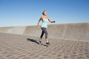 Active senior woman jogging on the pier