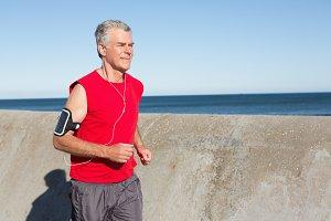 Active senior man jogging on the pier