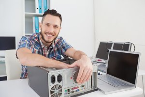 Computer engineer smiling at camera beside open console