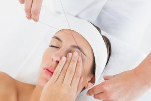 Hands threading beautiful womans eyebrow