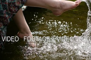 Girl talks feet in water splashes slow motion