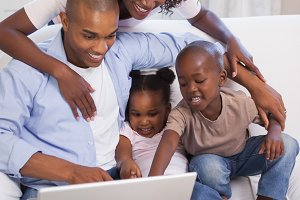 Happy family sitting on couch together using laptop