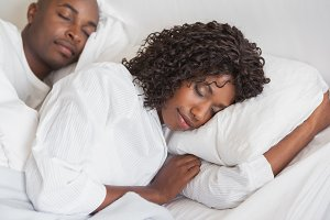 Happy couple sleeping together in bed