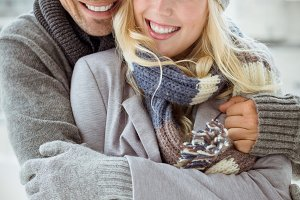 Cute couple in warm clothing smiling at camera