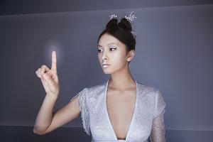 Future concept. Young pretty asian woman touching digital hologram